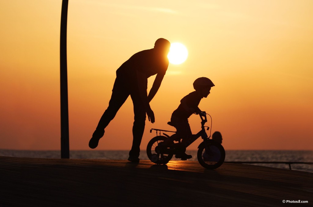 dad pushing son at sunset