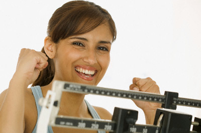 Young woman standing on a weighing scale with arms raised in excitement